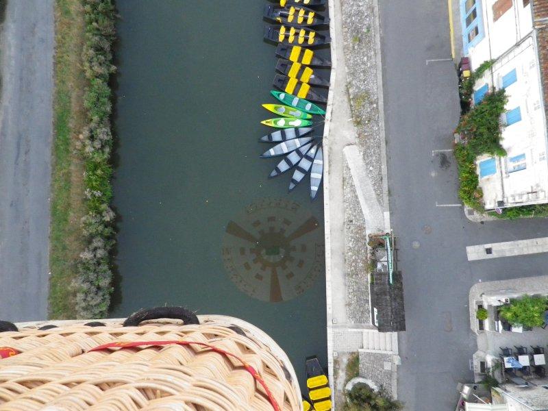 Montgolfière au-dessus d'un canal avec des barques colorées.