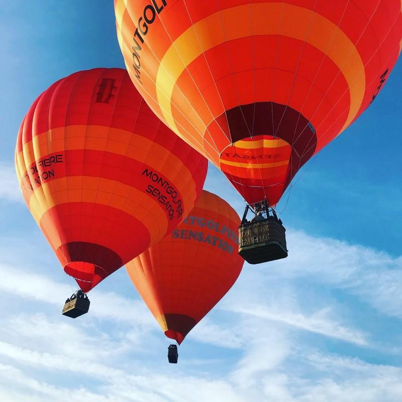 Trois montgolfières rouges et oranges dans le ciel
